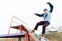 El patinador adolescente en un suéter con capucha y vaqueros resbala sobre una verja en un monopatín en un parque del patín Imagen de archivo libre de regalías