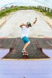 El patinador adolescente monta sobre una rampa en un monopatín en un parque del patín Fotos de archivo libres de regalías