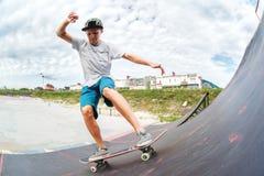El patinador adolescente monta sobre una rampa en un monopatín en un parque del patín Fotos de archivo