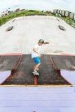 El patinador adolescente monta sobre una rampa en un monopatín en un parque del patín Imagen de archivo