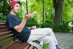 El patinador de pelo largo del inconformista en un casquillo se sienta en un banco y hace girar en un vuelta-hilandero fotografía de archivo libre de regalías