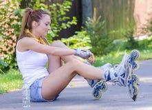 El patinador de sexo femenino joven ata sus rodillos Foto de archivo libre de regalías