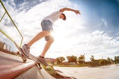 El patinador del adolescente en un casquillo y los pantalones cortos en los carriles en un monopatín en un patín parquean Foto de archivo