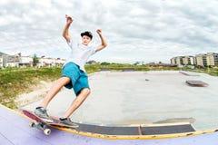 El patinador del adolescente en un casquillo y los pantalones cortos en los carriles en un monopatín en un patín parquean Foto de archivo libre de regalías