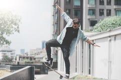 El patinador del muchacho está haciendo truco en la calle imágenes de archivo libres de regalías