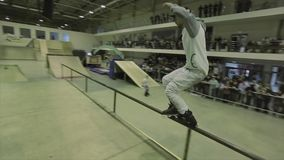 El patinador del rodillo en paseo del casquillo en la cerca, hace trucos salto Manía extrema Competencia en skatepark metrajes