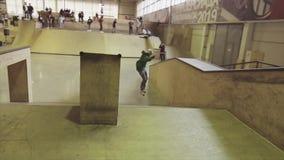 El patinador del rodillo en sudadera con capucha verde hace el salto, pies del gancho agarrador en aire Manía extrema Competencia metrajes