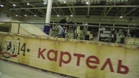 El patinador del rodillo hace el salto de altura, pies del gancho agarrador en aire trampolín Manía extrema Competencia en skatep almacen de metraje de vídeo