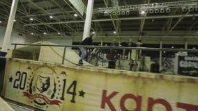 El patinador del rodillo hace el salto, pies del gancho agarrador en aire Rollo en la cerca Manía extrema Competencia en skatepar almacen de metraje de vídeo