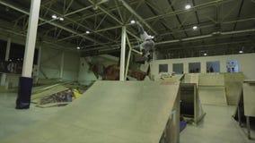 El patinador del rodillo hace el tirón 540 en aire, consigue derramamiento trampolín Manía extrema Competencia en skatepark metrajes