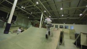 El patinador del rodillo hace el tirón 540 en aire trampolín Manía extrema Competencia en skatepark audiencias almacen de video