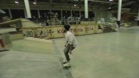 El patinador del rodillo hace el trampolín del salto, pie del gancho agarrador en aire Manía extrema Competencia en skatepark metrajes