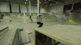 El patinador del rodillo hace salto fallado en el trampolín Manía extrema Competencia en skatepark Gente almacen de metraje de vídeo