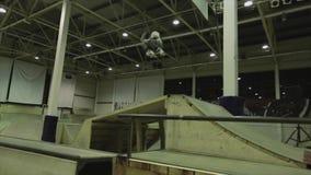 El patinador del rodillo hace varios tirones en aire trampolín Manía extrema Competencia en skatepark almacen de video