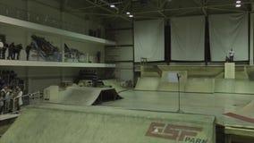 El patinador del rodillo salta en el trampolín Manía extrema Competencia en skatepark audiencias almacen de metraje de vídeo