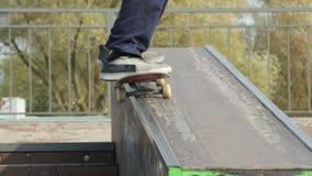 El patinador hace que 50-50 muele abajo la repisa en el skatepark, opinión del primer en a cámara lenta almacen de video