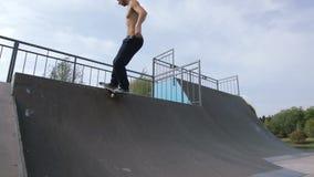El patinador hace el rollo de la roca n del truco al borde del tubo cuarto en skatepark de madera metrajes