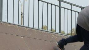 El patinador hace rutina del truco 50-50 en el borde del radio de la rampa, primer, a cámara lenta almacen de metraje de vídeo