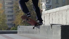 El patinador hace el truco de la rutina torcido en el granit conmemorativo, vídeo a cámara lenta metrajes
