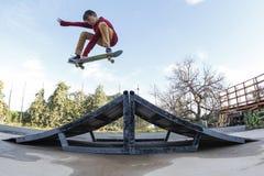 El patinador hace un salto y un gancho agarrador Imagenes de archivo