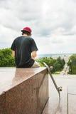 El patinador sienta con la suya la parte posterior y piensa al lado del monopatín Fotos de archivo libres de regalías