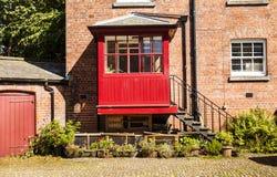 El patio con la casa y el hierro de ladrillo camina llevando a un po rojo Fotografía de archivo