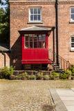 El patio con la casa y el hierro de ladrillo camina llevando a un po rojo Imagenes de archivo