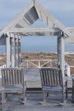 El patio de madera y dos sillas del eje de balancín pasan por alto el océano Imagen de archivo libre de regalías