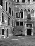 El patio medieval en Venecia con las ventanas viejas reparadas empareda a Imagenes de archivo