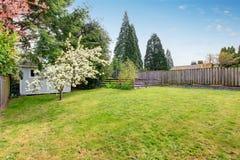El patio trasero cercado con la hierba llenó el jardín y la pequeña vertiente foto de archivo