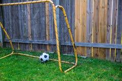 El patio trasero chldren fútbol en la cerca de madera con la pared Imagenes de archivo
