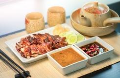 El pato asado con la salsa sirvió sobre la placa blanca en la estera de bambú natural foto de archivo libre de regalías