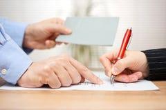 El patrón muestra a empleado donde firmar y dando su folleto en Fotos de archivo
