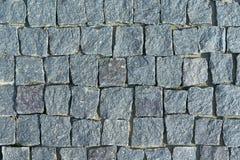 El pavimento puso con los adoquines de piedra cuadrados del granito Foto de archivo