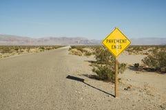 El pavimento termina la señal de tráfico en desierto Imágenes de archivo libres de regalías