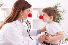 El payaso de sexo femenino adorable sonriente del doctor escucha corazón paciente Fotos de archivo libres de regalías
