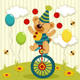 El payaso del oso hace juegos malabares y monta un unicycle Fotos de archivo libres de regalías