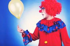 El payaso en traje rojo con el globo entonó imagen Fotografía de archivo libre de regalías