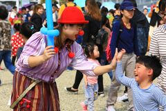 El payaso Girl está dando un alto-Cinco a Little Boy en una feria de la ciudad fotos de archivo libres de regalías