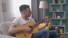 El PDA tirado de hombre joven toca la guitarra en su sala de estar acogedora almacen de video