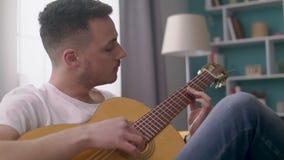 El PDA tirado de hombre toca la guitarra en su sala de estar acogedora metrajes