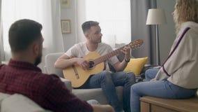 El PDA tirado de hombre toca la guitarra para sus amigos en una sala de estar acogedora almacen de metraje de vídeo