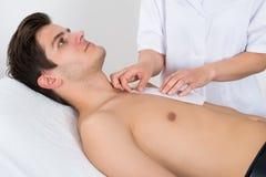 El pecho de Waxing Man del terapeuta de la belleza Imagen de archivo libre de regalías