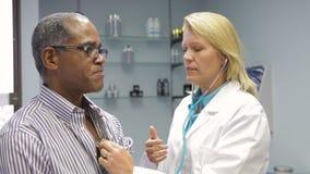 El pecho del paciente del doctor Listening To Male con el estetoscopio almacen de metraje de vídeo