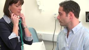 El pecho del paciente del doctor Listening To Male en cirugía almacen de metraje de vídeo