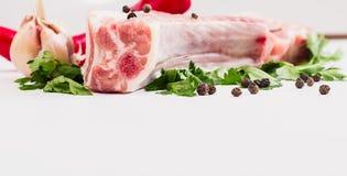 El pedazo de carne jugoso en el hueso con una vaina de la pimienta roja, el perejil y el ajo mienten en una tabla de madera Imagen de archivo libre de regalías