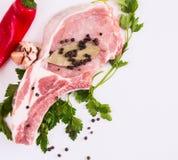 El pedazo de carne jugoso en el hueso con una vaina de la pimienta roja, el perejil y el ajo mienten en una tabla de madera Imágenes de archivo libres de regalías