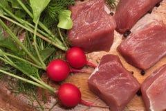 El pedazo de carne jugoso sirvi? en una placa de madera con el condimento, las hierbas y las verduras fotos de archivo libres de regalías