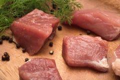 El pedazo de carne jugoso sirvi? en una placa de madera con el condimento y las hierbas foto de archivo