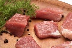 El pedazo de carne jugoso sirvi? en una placa de madera con el condimento y las hierbas imagen de archivo libre de regalías